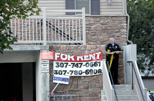 Logan City police officer Barry Parslow takes down a segment of crime scene tape at an apartment complex where two people were found dead early Monday, July 14, 2014, in Logan Utah.  Police say three people have been found shot dead in two different locations in Logan. Police say they responded to reports of gunfire at an apartment just after midnight.   Police say they found a man and a woman dead inside one of the units. Officers say they received another 911 call around 1 a.m. reporting a gunshot at a west Logan home and found a man dead of what appears to be a self-inflicted gunshot wound. Police suspect the two incidents are connected. (AP Photo/The Herald Journal,Amy Macavinta)