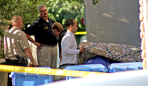 Morticians and Logan City police officers remove one of two gunshot victims from apartment complex Monday, July 14, 2014, in Logan, Utah.  Police say three people have been found shot dead in two different locations in Logan. Police say they responded to reports of gunfire at an apartment just after midnight.   Police say they found a man and a woman dead inside one of the units. Officers say they received another 911 call around 1 a.m. reporting a gunshot at a west Logan home and found a man dead of what appears to be a self-inflicted gunshot wound. Police suspect the two incidents are connected. (AP Photo/The Herald Journal, Jeff Hunter)