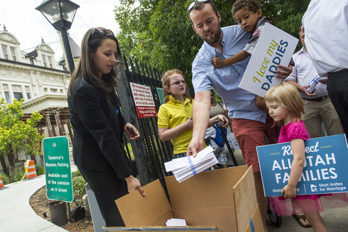 "Chris Detrick  |  The Salt Lake Tribune Weston Clark and his son Xander, 4, help to deliver signed petitions outside of the Governor's Mansion in Salt Lake City Wednesday July 9, 2014. Utah Unites for Marriage delivered more than 3,800 signatures collected on a petition urging Governor Gary Herbert and Attorney General Sean Reyes to end their ""relentless court fight to stop same-sex marriage and deny legally married couples recognition and access to second-parent adoptions."""
