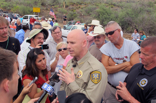 Pinal County Sheriff Paul Babeau speaks to the media as protesters gather near the entrance to juvenile facility in an effort to stop a bus load of Central American immigrant children from being delivered to the facility, Tuesday, July 15, 2014, in Oracle, Ariz. Federal officials delayed the bus with no details on whether the children will arrive or not. (AP Photo/Brian Skoloff)