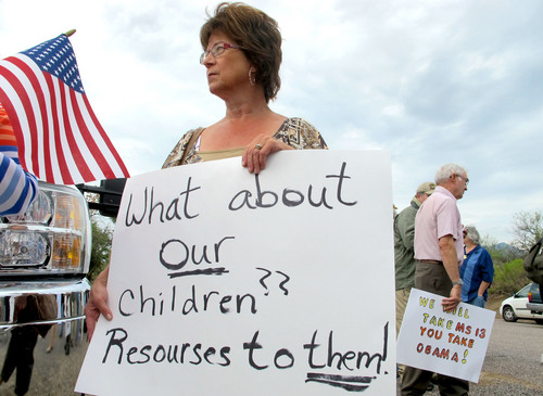 Protester Deborah Pfaff stands near the entrance to juvenile facility in an effort to stop a bus load of Central American immigrant children from being delivered to the facility, Tuesday, July 15, 2014, in Oracle, Ariz. Federal officials delayed the bus with no details on whether the children will arrive or not. (AP Photo/Brian Skoloff)