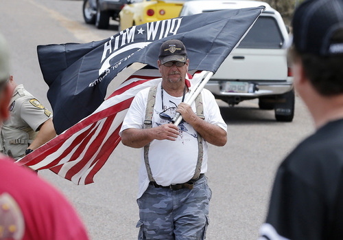 Protester Fred Puckett walks along the road near the entrance to juvenile facility in an effort to stop a bus load of Central American immigrant children from being delivered to the facility, Tuesday, July 15, 2014, in Oracle, Ariz. Federal officials delayed the bus with no details on whether the children will arrive or not. (AP Photo/Matt York)