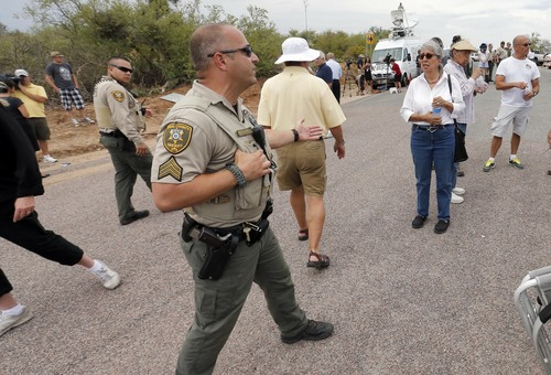 A Pinal County Sheriffs Deputy informs protesters that a bus load of Central American immigrant children will not arrive at a juvenile facility, Tuesday, July 15, 2014, in Oracle, Ariz. Federal officials delayed the bus with no details on whether the children will arrive or not. (AP Photo/Matt York)