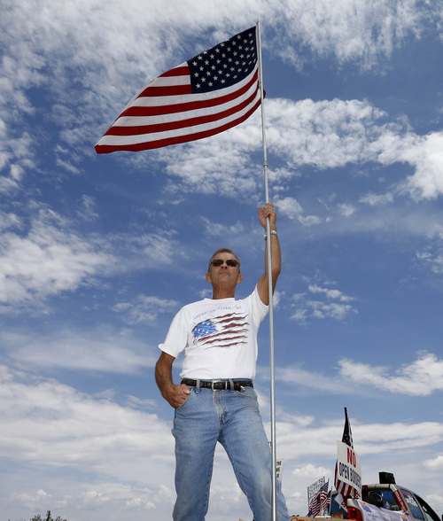 Bill Essenmacher protests near the entrance to as juvenile facility in an effort to stop a bus load of Central American immigrant children from being delivered to the facility, Tuesday, July 15, 2014, in Oracle, Ariz. Federal officials delayed the bus with no details on whether the children will arrive or not. (AP Photo/Matt York)