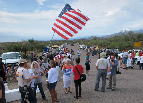 Protesters gather near the entrance to juvenile facility in an effort to stop a bus load of Central American immigrant children from being delivered to the facility, Tuesday, July 15, 2014, in Oracle, Ariz. Federal officials delayed the bus with no details on whether the children will arrive or not. (AP Photo/Brian Skoloff)