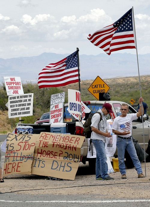 Protesters gather near the entrance to juvenile facility in an effort to stop a bus load of Central American immigrant children from being delivered to the facility, Tuesday, July 15, 2014, in Oracle, Ariz. Federal officials delayed the bus with no details on whether the children will arrive or not. (AP Photo/Matt York)