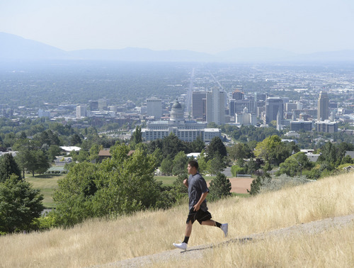 Al Hartmann  |  The Salt Lake Tribune  A hiker jogs down the path from Ensign Peak above Salt Lake City Tuesday, July 16.  With higher summer temperatures, ozone pollution was considered moderate but approaching the unhealthy level for sensitive groups.