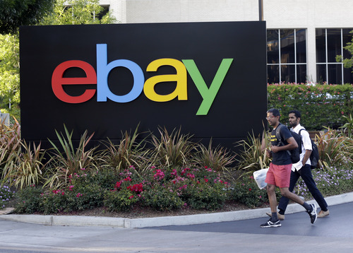 In this June 5, 2014 photo, people walk in front of an eBay Inc. sign at the company's headquarters in San Jose, Calif. EBay Inc. reports quarterly financial results on Wednesday, July 16, 2014. (AP Photo/Marcio Jose Sanchez)