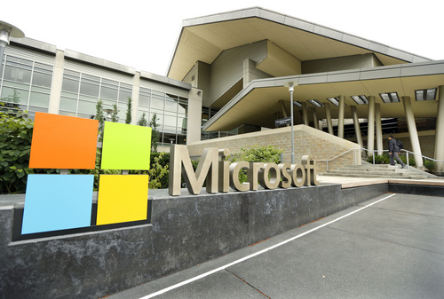 This July 3, 2014 photo shows Microsoft Corp. signage outside the Microsoft Visitor Center in Redmond, Wash. Microsoft on Thursday, July 17, 2014 announced it will lay off 18,000 workers over the next year. (AP Photo Ted S. Warren)