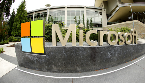 This photo taken with a fisheye lens on July 3, 2014 shows Microsoft Corp. signage outside the Microsoft Visitor Center in Redmond, Wash. Microsoft on Thursday, July 17, 2014 announced it will lay off 18,000 workers over the next year.  (AP Photo Ted S. Warren)