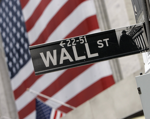 FILE - In this Aug. 16, 2007 file photo, the flags on the facade of the New York Stock Exchange are a backdrop for a Wall Street street sign. European stocks were lower after most Asian markets abandoned modest gains Thursday July 17, 2014 ahead of U.S. economic data and corporate earnings reports. (AP Photo/Richard Drew, file)