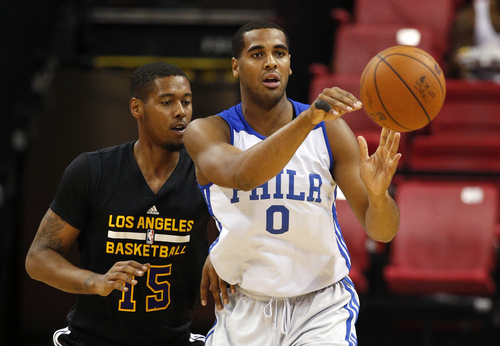 Philadelphia 76ers' Brandon Davies (0) passes the ball away from Los Angeles Lakers' Trey Thompkins during the first half of an NBA summer league basketball game Wednesday, July 16, 2014, in Las Vegas. (AP Photo/John Locher)