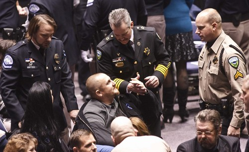 "Leah Hogsten | Tribune file photo   Weber County Sheriff's Sgt. Nate Hutchinson, injured in the drug raid shakes the hand of Weber County Sheriff Terry Thompson (center). Joined by law enforcement officers statewide, the family and friends of slain Ogden police Officer Jared Francom said farewell during Wednesday, January 11, 2012 funeral services at Weber State University's Dee Events Center. Francom, the 30-year-old father of two young girls, was gunned down during a drug raid on an Ogden home the night of Jan. 4. Five other officers also were wounded in a hail of gunfire that erupted as the Weber-Morgan Narcotics Strike Force attempted to serve a ""knock and announce"" search warrant on the residence of Matthew David Stewart."