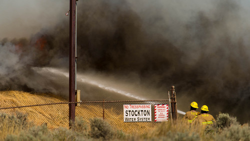 Trent Nelson  |  The Salt Lake Tribune Firefighters work to extinguish a fire in Stockton, Wednesday July 16, 2014.