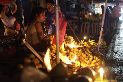 A Filipino vendor uses candles to illuminate bananas during a power outage a day after strong winds from Typhoon Rammasun damaged power supplies, in suburban Quezon city, north of Manila, Philippines, Thursday July 17, 2014. Parts of the capital and some provinces remain without power after Typhoon Rammasun barreled through northern Philippines leaving dozens of people dead and forcing more than half a million people to flee its lethal wind and rains, officials said Thursday. (AP Photo/Aaron Favila)