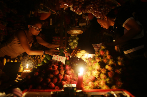 Filipino vendors arrange fruits as they use candles to illuminate them a day after strong winds from Typhoon Rammasun damaged power supplies, in suburban Quezon city, north of Manila, Philippines, Thursday July 17, 2014. Parts of the capital and some provinces remain without power after Typhoon Rammasun barreled through northern Philippines leaving dozens of people dead and forcing more than half a million people to flee its lethal wind and rains, officials said Thursday. (AP Photo/Aaron Favila)