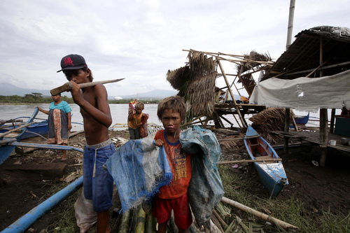 "Sea gypsies known as ""Badjaos"" stand by their damaged houses on stilts at the coastal village of Bajaoan, at Batangas city, 100 kilometers (62 miles) south of Manila, Philippines Thursday, July 17, 2014. Typhoon Rammasun (locally known as Glenda) ravaged central and northern Philippines, including this province, leaving dozens of people dead, knocking out power in many areas and damaging agriculture and infrastructure.(AP Photo/Bullit Marquez)"