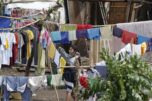 A resident hangs clothes to dry Thursday, July 17, 2014, a day after Typhoon Rammasun hit Batangas city, 100 kilometers (62 miles) south of Manila, Philippines. Typhoon Rammasun battered central and northern Philippines, knocking out power in many areas and damaged infrastructure. (AP Photo/Bullit Marquez)