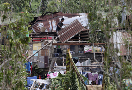 A resident fixes his house which was damaged by Typhoon Rammasun on Wednesday in Batangas city, 100 kilometers (62 miles) south of Manila, Philippines, Thursday, July 17, 2014. Typhoon Rammasun battered central and northern Philippines, knocking out power in many areas and damaged infrastructure. (AP Photo/Bullit Marquez)