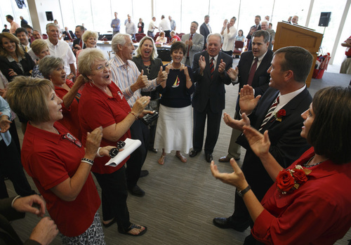 "Jud Burkett | The Spectrum & Daily News  Former Dixie State University President Stephen Nadauld, fourth from right, and his wife, Margaret, join Dixie State alumni and hall of fame member Delmont Truman as he gives two thumbs up while leading a group Dixie State dignitaries in a chorus of the song ""Are You From Dixie?"" as they welcome Richard ""Biff"" Williams, second from right, and his wife, Kristin to the campus shortly after the announcement was made naming Williams as the new president of Dixie State University Thursday, July 17, 2014."