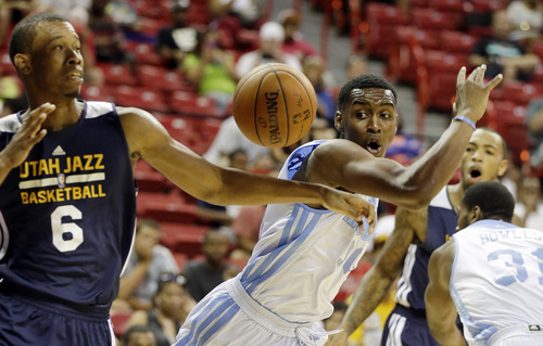 Utah Jazz's Rodney Hood (6) and Denver Nuggets' Quincy Miller (30) reach for a loose ball during the first half of an NBA summer league basketball game Tuesday, July 15, 2014, in Las Vegas. (AP Photo/Isaac Brekken)