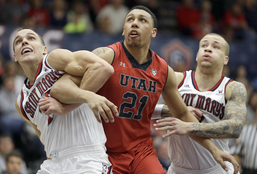 Utah forward Jordan Loveridge (21) battles for a rebound against  St. Mary's forward Beau Levesque, left, and guard Kerry Carter, right, during the first half of an NCAA college basketball game against Utah in the first round of the National Invitational Tournament in Moraga, Calif., Tuesday, March 18, 2014. (AP Photo/Tony Avelar)