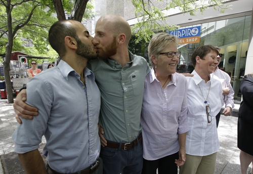 FILE - In this June 25, 2014, file photo, from left, Moudi Sbeity and Derek Kitchen kiss accompanied by fellow plaintiffs Laurie Wood and Kody Partridge at a news conference outside their lawyer's office in Salt Lake City. The 10th Circuit Court of Appeals in Denver ruled on June 25 that Utah must allow gay couples to marry, finding the Constitution protects same-sex relationships. The court made the same ruling on Oklahoma's ban Friday. Utah and Oklahoma voters overwhelmingly passed the bans in 2004. (AP Photo/Rick Bowmer, File)