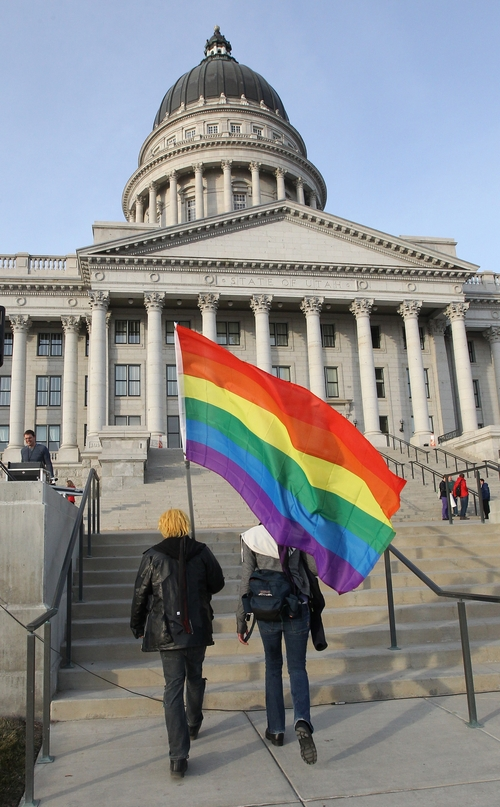 FILE - In this Jan. 28, 2014 file photo, gay marriage supporters Corbin Aoyagi, left, and Jerusha Cobb arrive with a rainbow flag for a rally at the Utah State Capitol in Salt Lake City. More than 1,000 gay and lesbian couples who married in Utah after the state same-sex marriage ban was overturned could get benefits in late July 2014 following a favorable ruling from a federal appeals court. On Friday, July 11, 2014, the 10th Circuit denied Utah's request for an indefinite delay. Instead, justices gave them only until July 21 to ask the U.S. Supreme Court to weigh in. (AP Photo/Rick Bowmer, File)