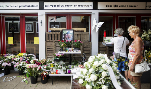 Women stand near to a portrait of Neeltje Tol, left, and Cor Schilder, right, placed with flowers and candles in front of their flower shop in Volendam, Netherlands, Saturday, July 19, 2014. An attack on a Malaysian jetliner shot down over Ukraine on Thursday killed 298 people from nearly a dozen nations, more than half being Dutch. Tol and Schilder were among those killed. (AP Photo/Phil Nijhuis)
