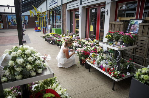 A portrait of Neeltje Tol, left, and Cor Schilder, right, is seen as a lady leaves flowers,  in front of their flower shop, in Volendam, Netherlands, Saturday, July 19, 2014. An attack on a Malaysian jetliner shot down over Ukraine on Thursday killed 298 people from nearly a dozen nations, more than half being Dutch.  Tol and Schilder were among those killed. (AP Photo/Phil Nijhuis)