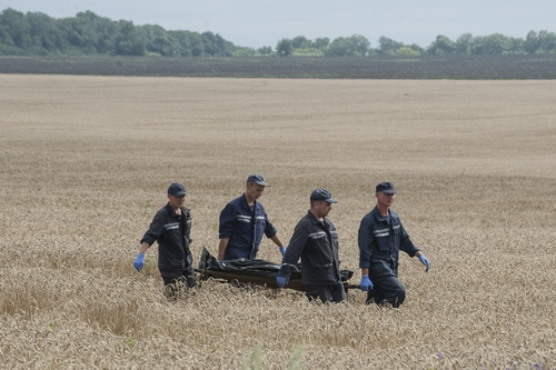 Emergency workers carry a stretcher with a victim's body in a bag at the crash site of a Malaysia Airlines jet near the village of Hrabove, eastern Ukraine, Saturday, July 19, 2014. Ukraine accused Russia on Saturday of helping separatist rebels destroy evidence at the crash site of a Malaysia Airlines plane shot down in rebel-held territory — a charge the rebels denied. (AP Photo/Evgeniy Maloletka)