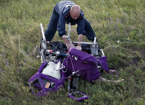 An emergency worker cuts through aircraft seat belts to free the body of a victim at the crash site of Malaysia Airlines Flight 17 near the village of Hrabove, eastern Ukraine, Saturday, July 19, 2014. International monitors moved gingerly Saturday through fields reeking of the decomposing corpses that fell from a Malaysian airliner shot down over rebel-held eastern Ukraine, trying to secure the sprawling site in hopes that a credible investigation can be conducted. (AP Photo/Vadim Ghirda)