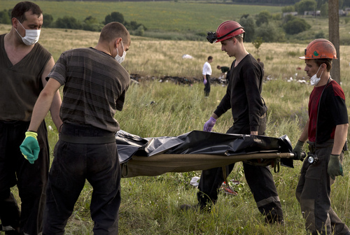 Ukrainian miners carry the body of a victim at the crash site of Malaysia Airlines Flight 17 near the village of Hrabove, eastern Ukraine, Saturday, July 19, 2014. World leaders demanded Friday that pro-Russia rebels who control the eastern Ukraine crash site of Malaysia Airlines Flight 17 give immediate, unfettered access to independent investigators to determine who shot down the plane. (AP Photo/Vadim Ghirda)