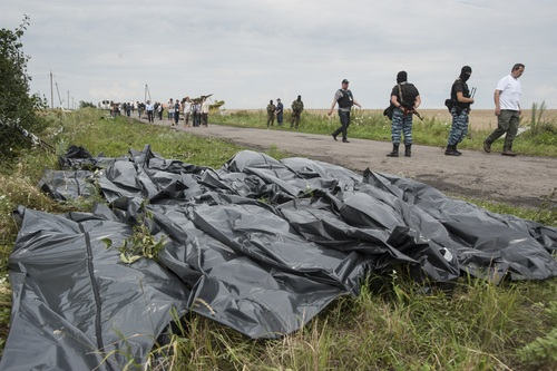 Pro-Russian fighters walk on a road with victims' bodies lying in bags by the side at the crash site of a Malaysia Airlines jet near the village of Hrabove, eastern Ukraine, Saturday, July 19, 2014. Ukraine accused Russia on Saturday of helping separatist rebels destroy evidence at the crash site of a Malaysia Airlines plane shot down in rebel-held territory — a charge the rebels denied. (AP Photo/Evgeniy Maloletka)