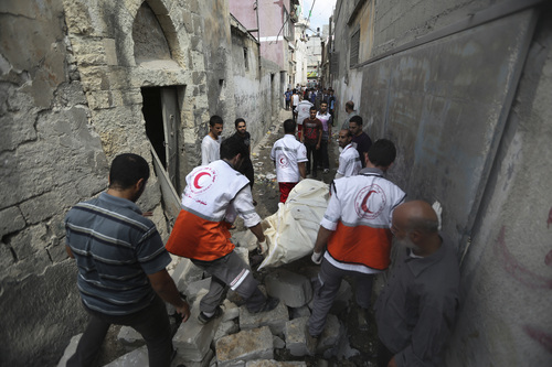 Palestinian medics carry a dead body found under the rubble of a home destroyed by an Israeli strike in the Shajaiyeh neighborhood of Gaza City, northern Gaza Strip, Sunday, July 20, 2014. Hundreds of panicked residents have fled the neighborhood which they say has come under heavy tank fire from Israeli forces. Some reported seeing dead and wounded in the streets, with ambulances unable to reach the area. Israel widened its ground offensive early Sunday, sending more troops into the Hamas-ruled territory to destroy tunnels used by the Islamic militants to try to sneak into Israel. (AP Photo/Hatem Moussa)