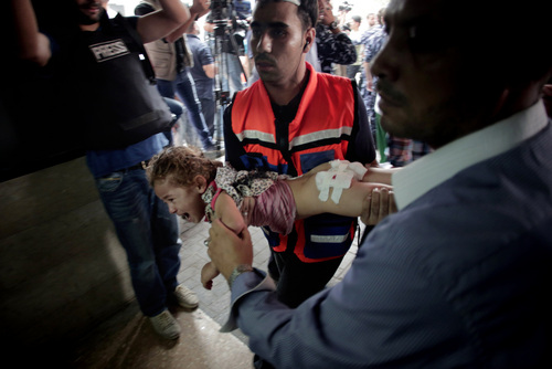 A Palestinian medic carries an injured girl to an emergency room at Shifa hospital in Gaza City, Sunday, July 20, 2014. A new wave of casualties arrives after daybreak Sunday, following a night of heavy Israeli tank fire on Gaza City's Shijaiyah neighborhood. Hospital guards shout at drivers to move to make room for the next vehicles, pushing back journalists and onlookers. (AP Photo/Khalil Hamra)
