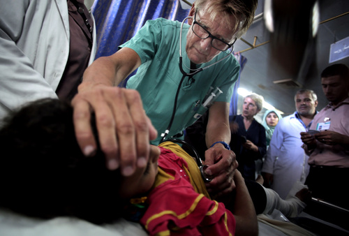 "In this Wednesday, July, 16, 2014, Mads Gilbert, Norwegian doctor who has volunteered at Shifa on and off for 17 years, treats a Palestinian girls at the emergency room of the Shifa hospital in Gaza City. Working at Shifa requires ingenuity. The power goes off repeatedly as aging hospital generators buckle under daily rolling blackouts Gaza residents have lived with for years. ""If we are in the middle of an operation (and) lights go out, what do the Palestinians do? They pick up their phones, and they use the light from the screen to illuminate the operation field,"" said Gilbert. (AP Photo/Khalil Hamra)"