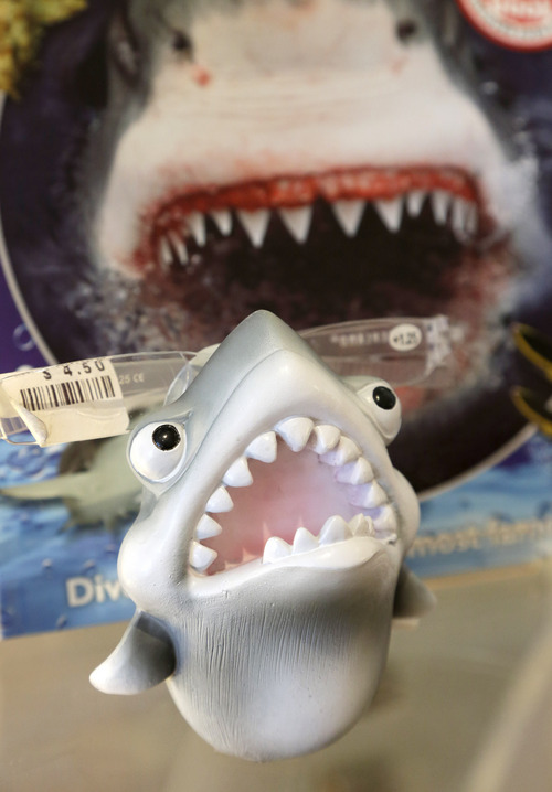 In this July 2, 2014 photo, an eye glass holder in the shape of a shark rests on a shelf in a souvenir shop in Chatham, Mass. With growing sightings of great white sharks off Cape Cod, local entrepreneurs are feeding the frenzy with their shark-themed memorabilia and apparel. (AP Photo/Steven Senne)
