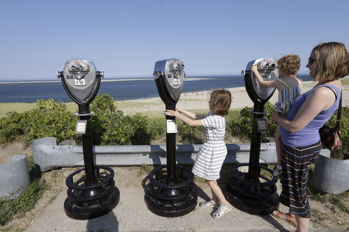 In this July 2, 2014 photo, Molly Saint-James, of Baltimore, right, helps her daughters Ellie McDonald, left, 6, and Poppy McDonald, 3, use telescopic viewers overlooking a beach while on vacation in Chatham, Mass. Growing sightings of great white sharks off Cape Cod are generating business for local entrepreneurs as residents and tourists seek get a glimpse of the offshore predators -- and purchase their shark-themed memorabilia. (AP Photo/Steven Senne)