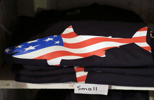 In this July 2, 2014 photo, a T-shirt with a likeness of a shark incorporating an American flag rests on a shelf in a souvenir shop in Chatham, Mass. With growing sightings of great white sharks off Cape Cod, local entrepreneurs are feeding the frenzy with their shark-themed memorabilia and apparel. (AP Photo/Steven Senne)