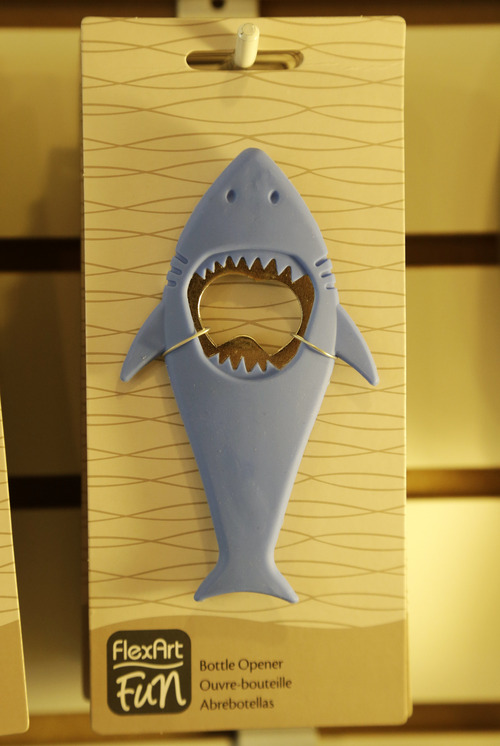 In this July 2, 2014 photo, a bottle opener in the likeness of a shark hangs from a hook in a souvenir shop in Chatham, Mass. With growing sightings of great white sharks off Cape Cod, local entrepreneurs are feeding the frenzy with their shark-themed memorabilia and apparel. (AP Photo/Steven Senne)