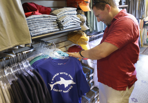 In this July 2, 2014 photo, vacationer Mark McCurdy, of Everett, Mass., examines shark-themed clothing at the Chatham Clothing Bar in Chatham, Mass. Growing sightings of great white sharks off Cape Cod are generating business for local entrepreneurs as residents and tourists seek a glimpse of the offshore predators -- or purchase their shark-themed memorabilia and apparel. (AP Photo/Steven Senne)