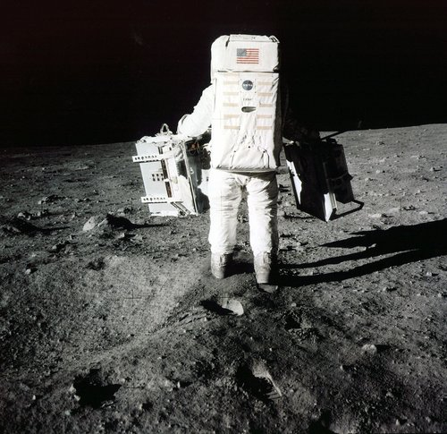 "Edwin ""Buzz"" Aldrin carries scientific experiments to a deployment site south of the lunar module Eagle. One experiment involved the inner composition of the moon, and another tried to determine the exact distance from Earth. Photo was taken by Neil Armstrong of the Apollo 11 mission on July 20, 1969.  (AP Photo/NASA/Neil Armstrong)"