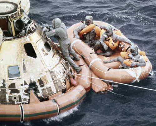 U.S. Navy personnel, protected by Biological Isolation Garments, are recovering the Apollo 11 crew from the re-entry vehicle, which landed safely in the Pacific Ocean on July 24, 1969, after an eight day mission on the moon. (AP Photo)