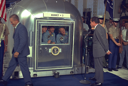 "President Richard Nixon looks at the Apollo 11 astronauts in the isolation unit aboard the USS Hornet after splashdown and recovery, July 24, 1969.  The astronauts, left to right, are:  Neil Armstrong,  Michael Collins and Edwin ""Buzz"" Aldrin.  (AP Photo)"