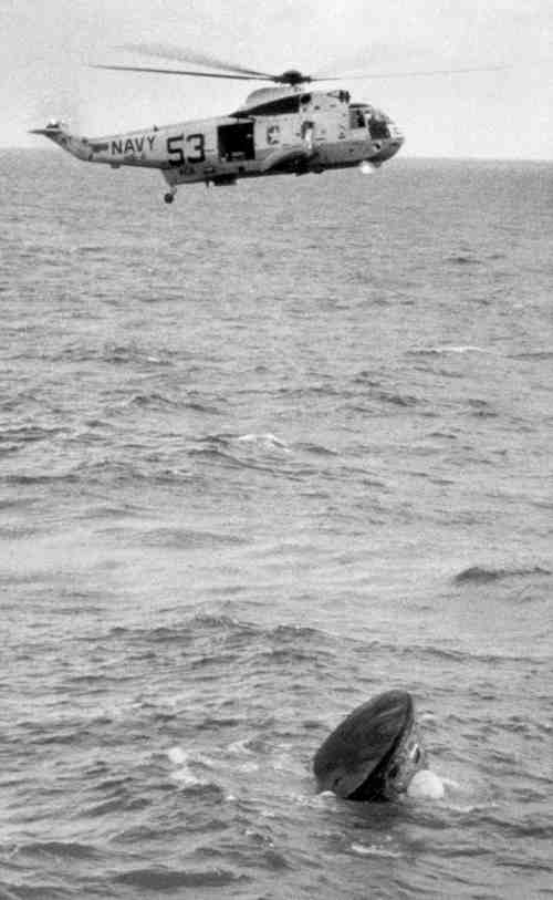 After an eight day mission on the moon, the Apollo 11 command module lands in the Pacific Ocean and is about to be safely recovered by U.S. Navy helicopters on July 24, 1969. (AP Photo)