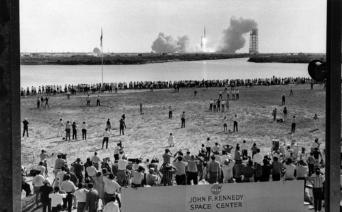 Thousands of newsmen and photographers line the banks of a lagoon at the Cape Kennedy Press Site on July 16, 1969 as the Saturn 5 Rocket with Apollo 11 astronauts aboard thunders from its launch pad three and a half miles away.