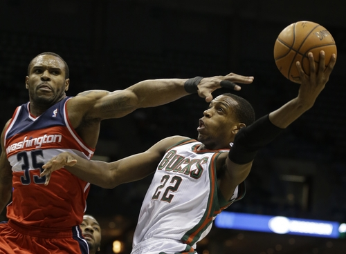 Milwaukee Bucks' Khris Middleton (22) drives against Washington Wizards' Trevor Booker during the second half of an NBA basketball game on Saturday, March 8, 2014, in Milwaukee. (AP Photo/Jeffrey Phelps)