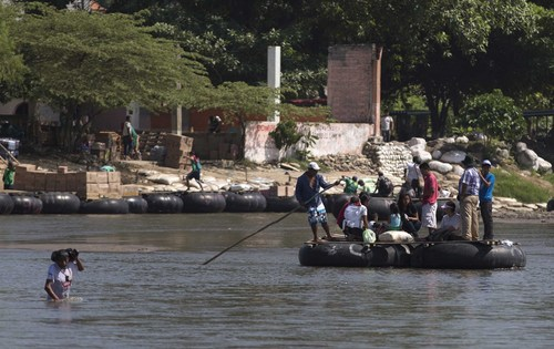 In this Friday, July 11, 2014 photo, people cross the Suchiate river that separates, Tecun Uman, Guatemala, from Ciudad Hidalgo, Mexico, aboard makeshift rafts made from truck inner tubes lashed to wooden boards. Scores of Central American migrants pay a modest fee crossing the river on these improvised rafts. (AP Photo/Eduardo Verdugo)