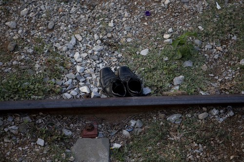 In this Saturday, July 12, 2014 photo, shoes are seen beside the train tracks in Ixtepec, Mexico. Migrants pay thousands of dollars per person for the illegal journey across thousands of miles in the care of smuggling networks that in turn pays off government officials, gangs operating on trains and drug cartels controlling the routes north. (AP Photo/Eduardo Verdugo)
